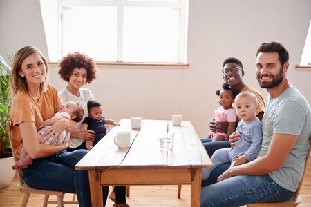 Portrait Of Two Families With Babies Meeting Around Table On Play Date At Home