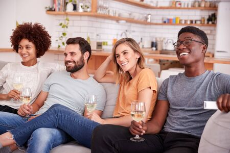 Group Of Friends Sitting On Sofa And Watching Movie At Home Whilst Drinking Wine Foto de archivo - 124543167