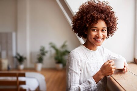 Portrait Of Young Woman Relaxing In Loft Apartment Looking Out Of Window With Hot Drink
