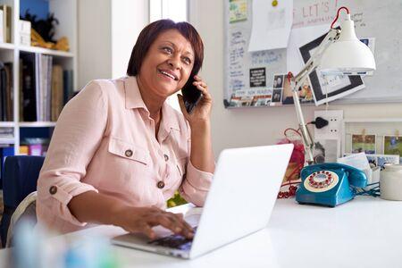 Femme mûre avec ordinateur portable travaillant au bureau à domicile à l'aide de téléphone mobile