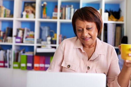 Smiling Mature Woman With Laptop Working In Home Office Imagens