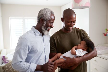 Proud Grandfather With Adult Son Cuddling Baby Grandson In Nursery At Home Imagens