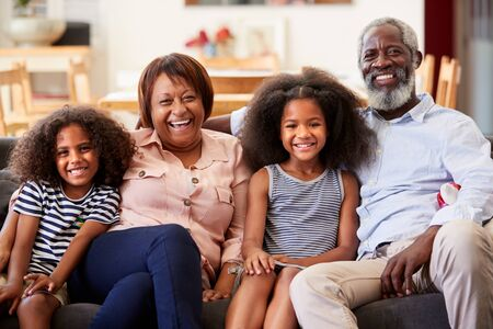 Portrait Of Smiling Grandparents With Grandchildren Sitting On Sofa At Home Relaxing Together