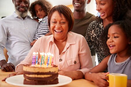 Multi-Generation Family Celebrating Grandmothers Birthday At Home With Cake And Candles Imagens