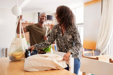 Couple Returning Home From Shopping Trip Unpacking Plastic Free Grocery Bags Imagens