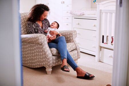 Loving Mother Sitting In Chair Cuddling Baby Son In Nursery At Home Imagens