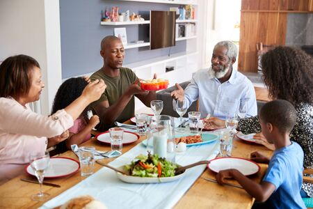 Multi-Generation Family Sitting Around Table At Home Enjoying Meal Together Imagens