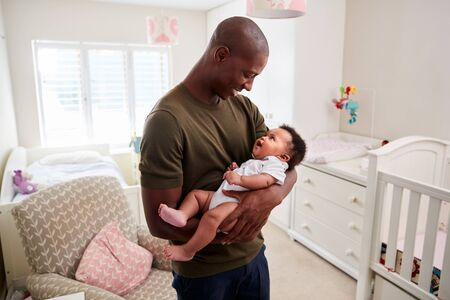 Proud Father Cuddling Baby Son In Nursery At Home Imagens