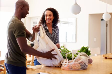 Couple Returning Home From Shopping Trip Unpacking Plastic Free Grocery Bags Stock Photo