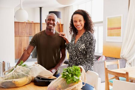 Portrait Of Couple Returning Home From Shopping Trip Unpacking Plastic Free Grocery Bags