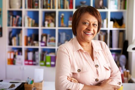 Portrait Of Smiling Mature Woman In Home Office By Bookcase Imagens