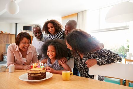Multi-Generation Family Celebrating Granddaughters Birthday At Home With Cake And Candles Imagens