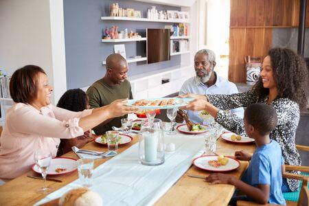 Familia de varias generaciones sentados alrededor de la mesa en casa disfrutando de la comida juntos