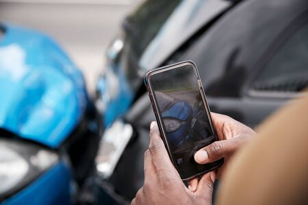 Male Motorist Involved In Car Accident Taking Picture Of Damage For Insurance Claim Imagens