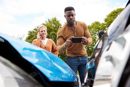 Männlicher Autofahrer, der in einen Autounfall verwickelt ist, um Schaden für Versicherungsanspruch zu fotografieren