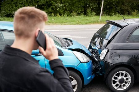 Young Male Motorist Involved In Car Accident Calling Insurance Company Or Recovery Service Stock Photo
