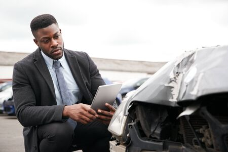 Male Insurance Loss Adjuster With Digital Tablet Inspecting Damage To Car From Motor Accident Reklamní fotografie