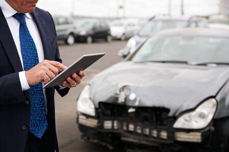 Ajustador de pérdidas de seguros masculino con tableta digital inspeccionando daños en el automóvil por accidente de motor Foto de archivo