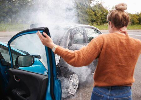 Rückansicht des weiblichen Autofahrers mit Kopfverletzungen aus dem Auto nach Crash