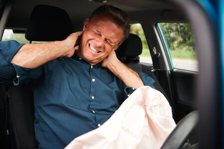 Male Motorist With Whiplash Injury In Car Crash With Airbag Deployed Stock Photo