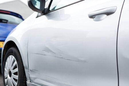 Detail van schade aan deur van voertuig in parkeerplaats met bekrast paneel