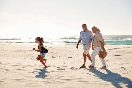 Älteres weißes Paar und ihre Enkelin zu Fuß an einem sonnigen Strand, Seitenansicht