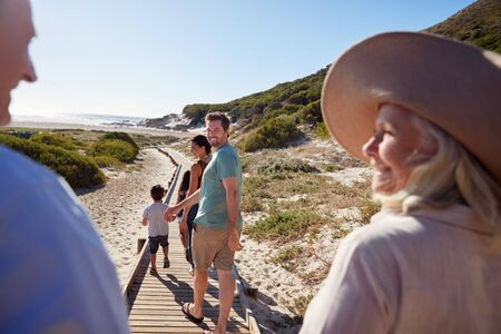Three generation white family walking on a beach, grandparents in the foreground, over shoulder view