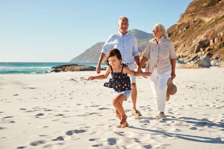 Älteres weißes Paar und ihre Enkelin zu Fuß an einem sonnigen Strand, Nahaufnahme Standard-Bild
