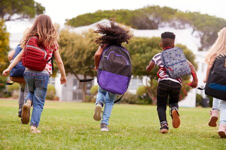 Rear View Of  Elementary School Pupils Running Across Field At Break Time