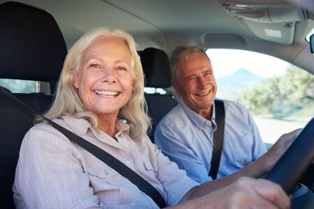 Senior white woman and her husband driving in their car smiling to camera, close up, side view