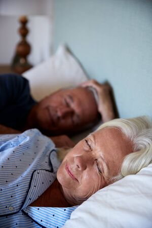 Senior white couple asleep in their bed, waist up, close up, vertical