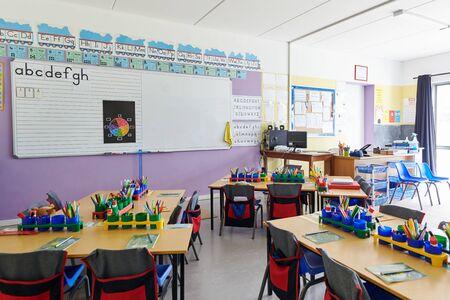 Classe vide à l'école primaire avec tableau blanc et bureaux