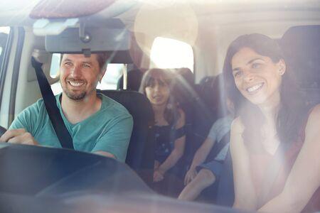 Junge weiße vierköpfige Familie, die sich in ihrem Auto auf den Weg macht, gesehen durch die Frontscheibe