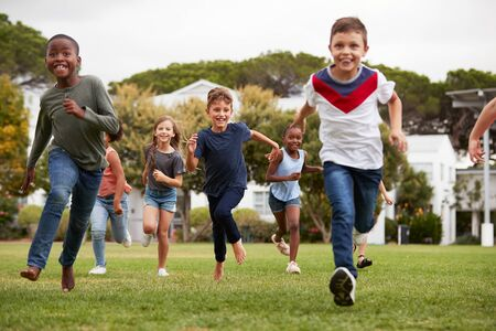 Excited Elementary School Pupils Running Across Field At Break Time