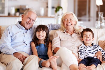 White senior couple and their grandchildren sitting on a sofa together at home smiling to camera Фото со стока