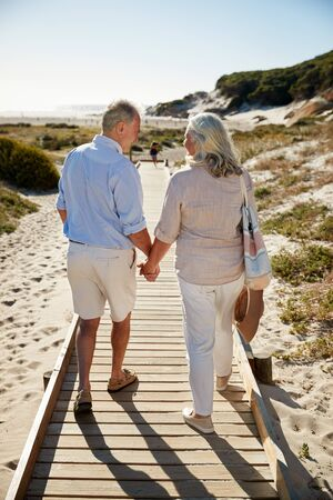 Senior white couple walking along wooden promenade on a beach holding hands, full length, back view Stockfoto