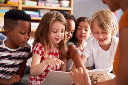 Groep basisschoolleerlingen die op de vloer zitten te luisteren naar de vrouwelijke leraar die het verhaal leest Stockfoto