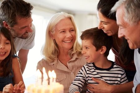 Four year old white boy and his family celebrating with a birthday cake and lit candles, close up