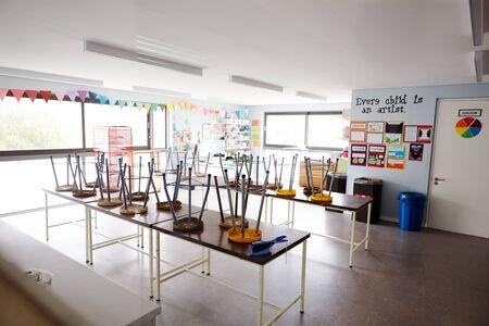 Aula de arte vacía en la escuela primaria con sillas apiladas en mesas Foto de archivo