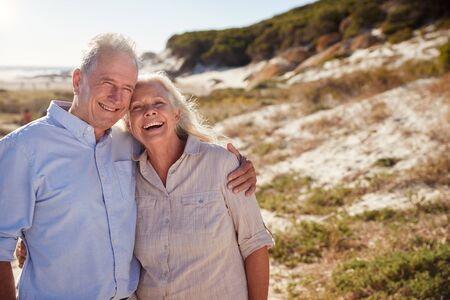 Senior white couple standing on a beach embracing and smiling to camera, close up