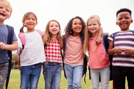 Retrato de emocionados alumnos de la escuela primaria en el campo de juego en el tiempo de descanso