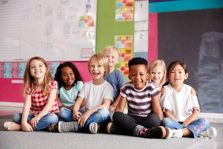 Ritratto di alunni delle scuole elementari seduti sul pavimento in aula