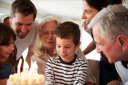 Four year old white boy and his family celebrating his birthday with cake and lit candles, close up 写真素材