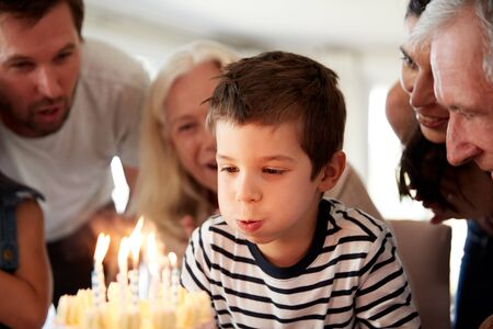 Four year old white boy celebrating with family blowing out candles on his birthday cake, close up