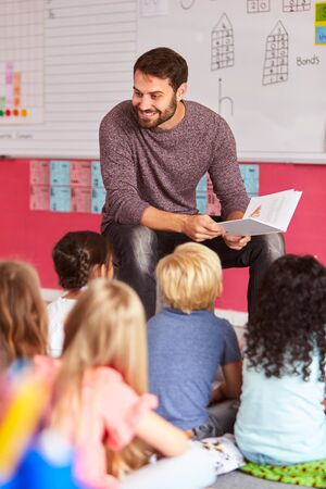 Male Teacher Reading Story To Group Of Elementary Pupils In School Classroom Stock Photo