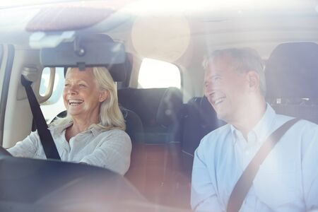 Happy senior white woman driving, her husband in front passenger seat, seen through front windscreen