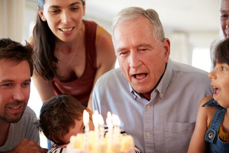 Senior white man celebrating with his family blowing out the candles on birthday cake, close up 写真素材