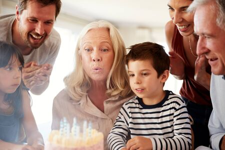Senior white woman celebrating her birthday with family blowing out the candles on her cake