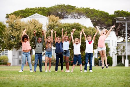 Group Of Excited Elementary School Pupils Standing On Playing Field At Break Time With Arms Raised Banco de Imagens