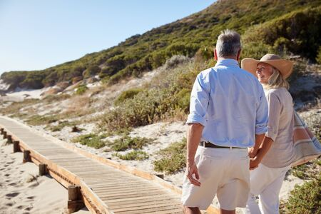 Senior white couple walking along a wooden promenade on a beach holding hands, close up, back view